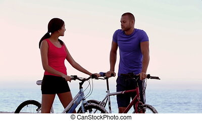 Friends with mountain bike on the beach talking together