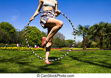 Young woman with hula hoop in park