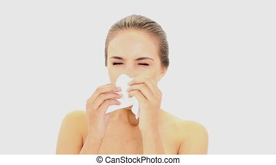 Beautiful model sneezing into a tissue on white background