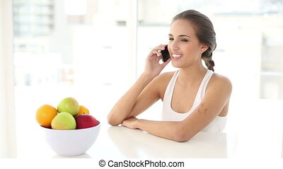 Beautiful young woman talking on her phone at home at the...