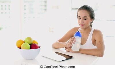 Beautiful young woman taking a drink after working out at...