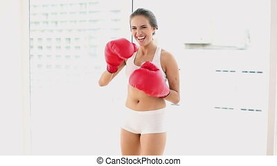 Beautiful young woman punching with red boxing gloves at...