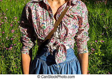Young woman in retro clothing standing in field