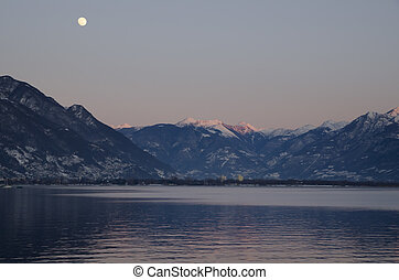 Full moon and snow-capped mountain in sunset with pink sky...
