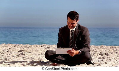 Unstressed businessman using tablet pc on the beach during...