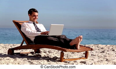 Unstressed businessman using laptop on the beach laying on a...