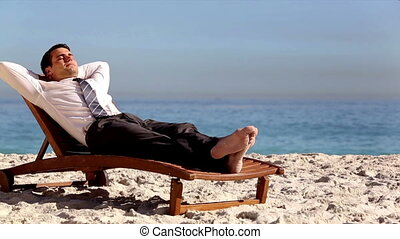 Unstressed businessman relaxing on the beach on a deck chair