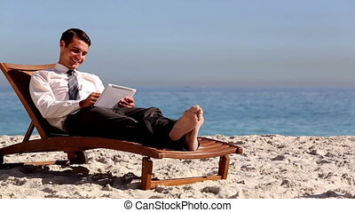 Unstressed businessman relaxing with a tablet pc on a deck...
