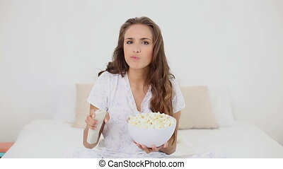 Young woman eating bowl of popcorn on bed and watching tv in...