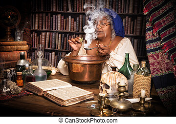 Smoking cauldron - Vintage alchemist adding herbs to a...