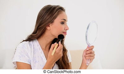 Young woman putting powder on her face and looking in hand...