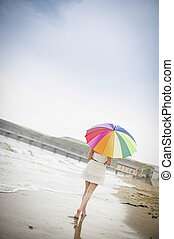 Woman walking along the beach with an umbrella - Woman...