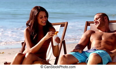 Cheerful woman applying sunscreen to her boyfriend on the...