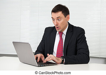 shocked young business man looking on his laptop computer