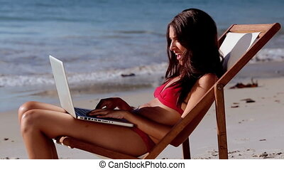 Brunette woman wearing bikini and using her laptop