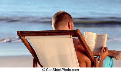 Man reading on the beach - Man reading a book on the beach