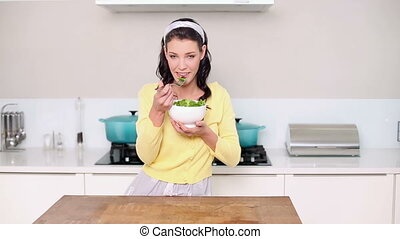 Beautiful brunette eating a bowl of salad