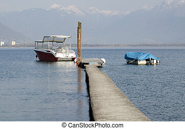 Boats on a pier and snow-capped mountains on lake maggiore...