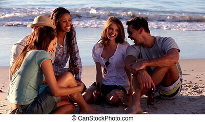 Group of friends clinking on the beach