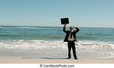 Happy businessman throwing his suitcase on the beach in slow...