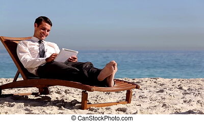 Businessman lying on the beach