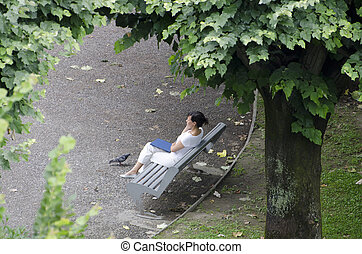 Woman resting on a bench - Woman sitting down on a bench...