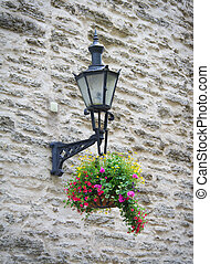 Old lantern with flowers in old town