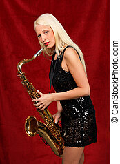 Young beautiful woman playing saxophone - Young blonde woman...
