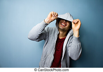 Happy man laughing from under his hoodie