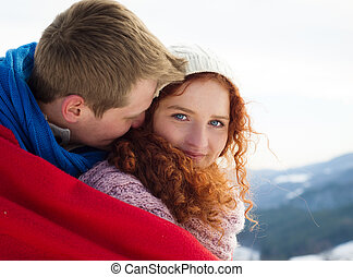 Winter love - Happy young couple in mountains at winter...