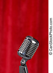 Microphone before a red curtain - Silver microphone in front...