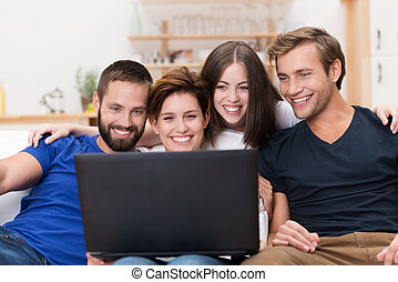 Group of friends laughing at a laptop - Group of friends...