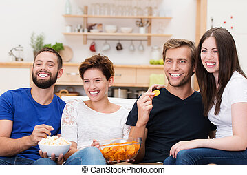 Laughing group of friends watching television