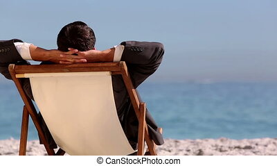Businessman relaxing on the beach and looking at the sea