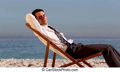 Businessman sleeping on the beach