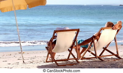Couple sitting on the beach - Couple sitting under parasol...