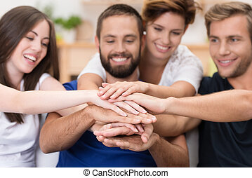 Friends stacking hands - Group of happy smiling young...
