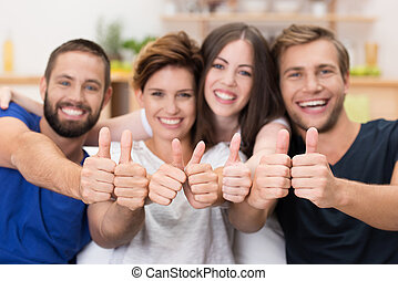 Young men and women giving a thumbs up - Attractive group of...