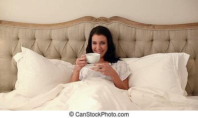 Beautiful brunette lying in bed