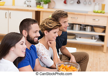 Group of young friends watching television sitting together...