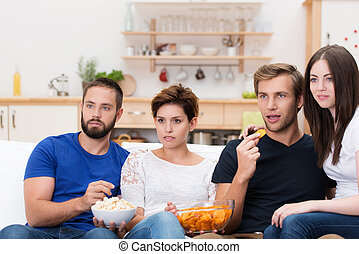 Group of friends watching a gripping movie