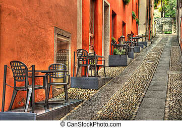 Alley with tables - Stone alley with tables and chairs in...