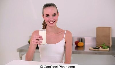 Smiling model drinking glass of milk at home in the kitchen