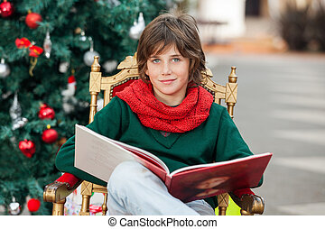 Boy With Book Sitting Against Christmas Tree - Portrait of...
