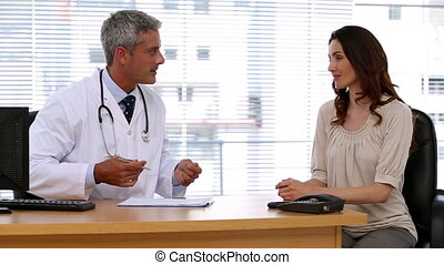 Doctor asking a patient about her symptoms in his office