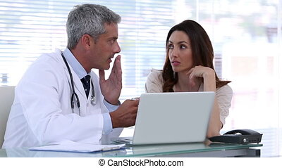 Doctor explaining a patient disease with a laptop in his...