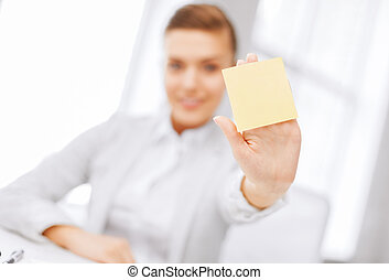 smiling businesswoman showing sticky note