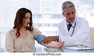 Doctor checking blood pressure of his patient in the...