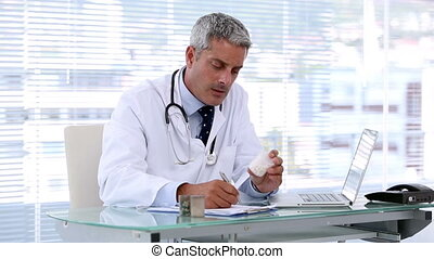 Doctor looking at pills while writing a prescription in his...