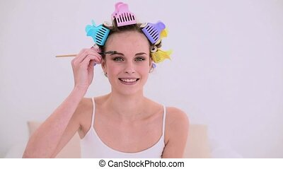Young model in hair rollers brushing her eyebrows at home in...